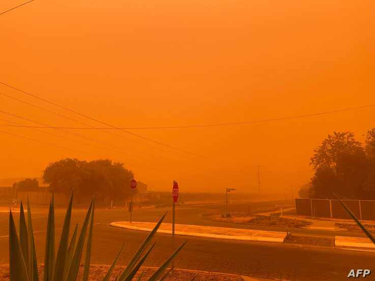This handout picture taken and released courtesy of Petra Johansson on November 21, 2019 shows the sky turning orange from dust…