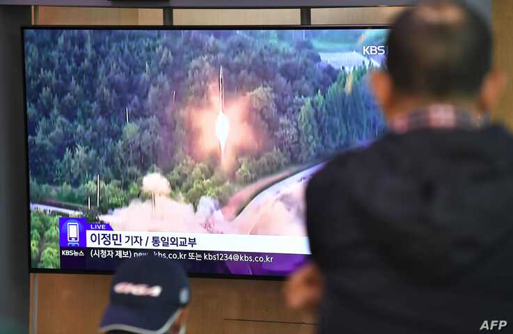 People watch a television news screen showing file footage of a North Korean missile launch, at a railway station in Seoul on…