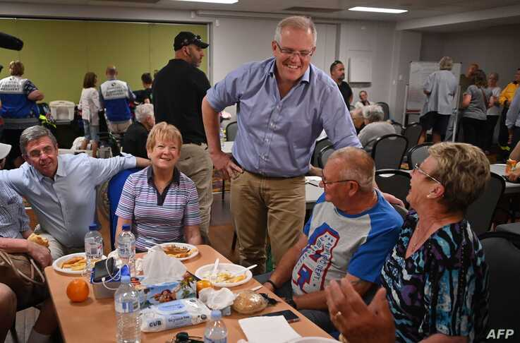 Australian Prime Minister Scott Morrison (L) speaks to residents at an evacauation centre in Taree, 350km north of Sydney on…