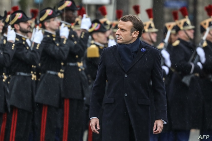 French President Emmanuel Macron reviews troops during a ceremony at the Arc de Triomphe in Paris