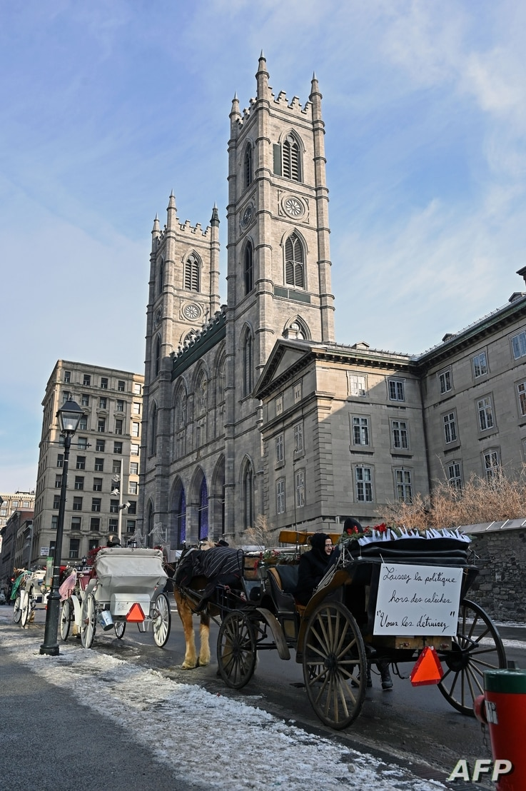 Horse-drawn carriages line up in front of the Notre-Dame basilica in Old-Montreal, waiting for tourists in Montreal, Quebec,…