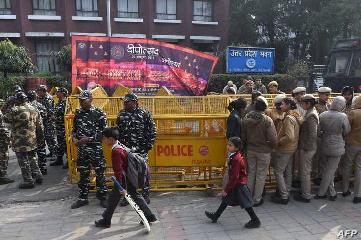 Schoolchildren walk past police outside the Uttar Pradesh Bhawan (state house) during a demonstration against the crackdown on…