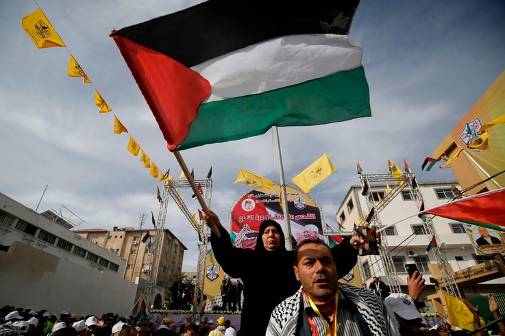 Supporters of the Palestinian Fatah movement take part in a rally marking the 55th foundation anniversary of the political...