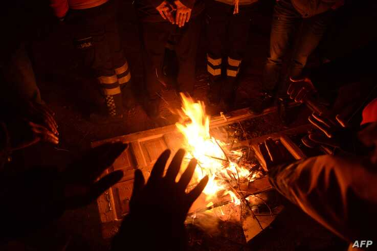 Turkish officials and police try to keep warm at the scene of a collapsed building following a 6.8 magnitude earthquake in…