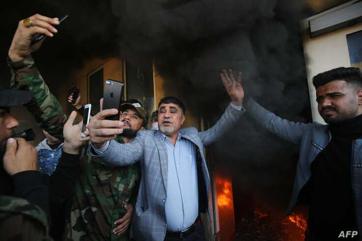 A commander of Iraq's Hashed al-Shaabi Jawad al-Talaibawi (C) takes a selfie at a gate of the US embassy in the capital Baghdad…