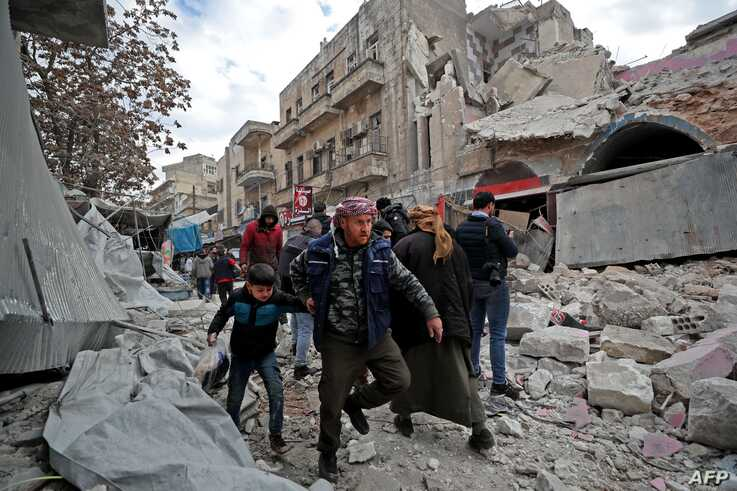 Syrians gather at the site of a regime air strike in Ariha town in Syria's last major opposition bastion of Idlib on January 15…