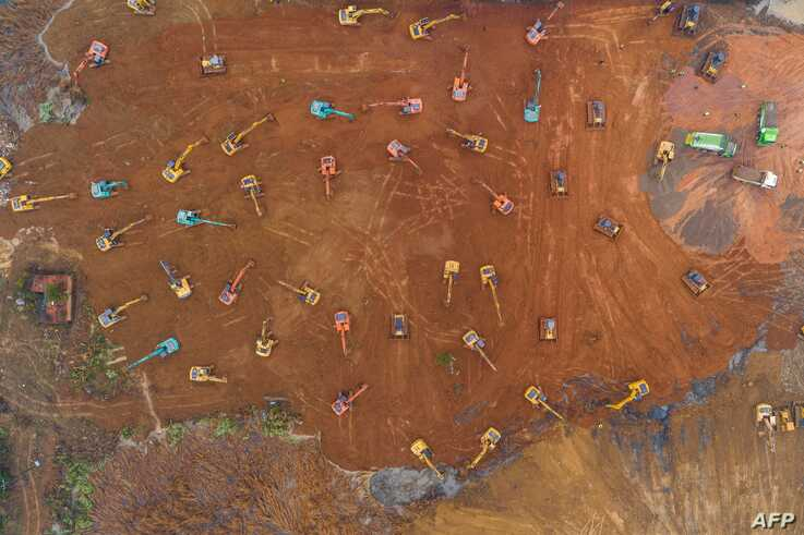 TOPSHOT - This aerial photo on January 24, 2020 shows excavators at the construction site of a new hospital being built to…