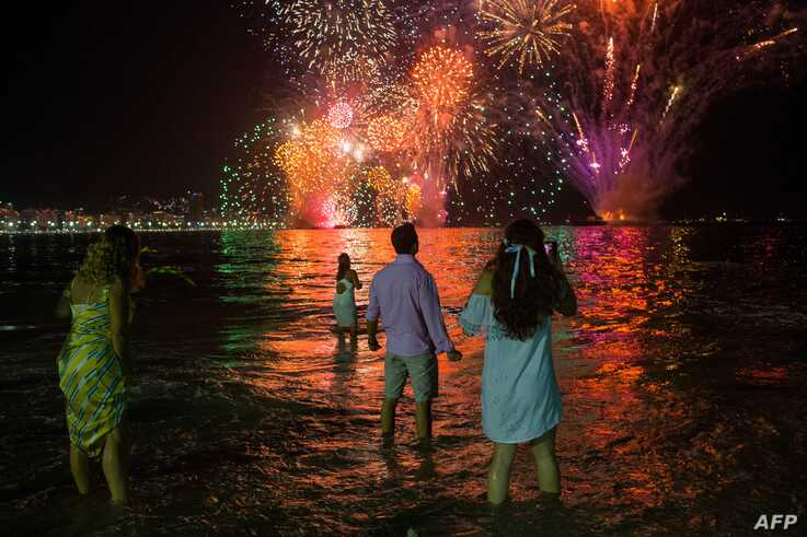 People celebrate as they watch the traditional New Year's fireworks at Copacabana Beach in Rio de Janeiro, Brazil, on December…