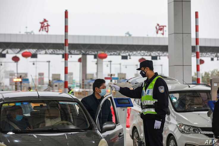 A police officer checks the temperature of a driver at a highway in Wuhan, in China's central Hubei province, on January 24,…