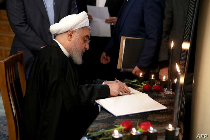 A handout picture provided by the Iranian Presidency on January 15, 2020 shows President Hassan Rouhani signing a book carrying…