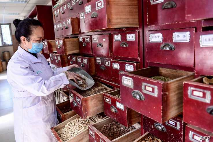 This photo taken on February 20, 2020 shows a medical worker taking a prescription of traditional Chinese medicine at a…