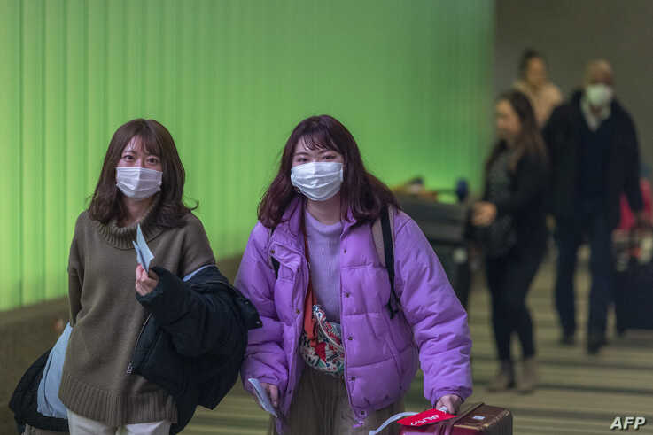 LOS ANGELES, CA - FEBRUARY 02: Travelers arrive to LAX Tom Bradley International Terminal wearing medical masks for protection…