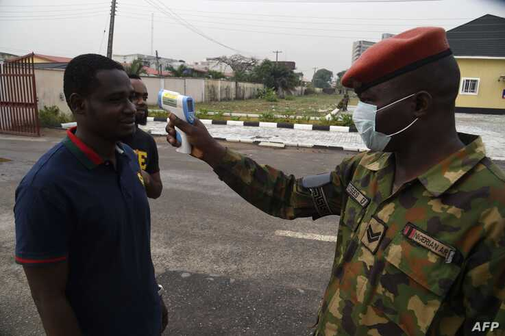 A soldier checks the body temperature of a visitor to the 68 Nigerian Army Reference Hospital at Yaba in Lagos, on February 28,…