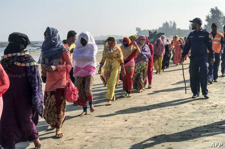 Coast guards escort Rohingya refugees following a boat capsizing accident, in Teknaf on February 11, 2020. - At least 15 people…