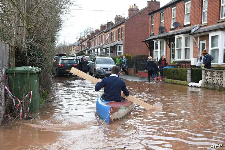 A man uses a plank of wood to paddle a kayak on flood water after the River Wye burst its banks in Ross-on-Wye, western England…
