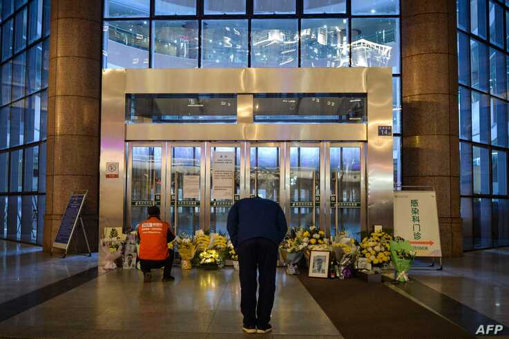 This photo taken on February 7, 2020 shows a man bowing in front of flowers and a photo of the late ophthalmologist Li Wenliang…