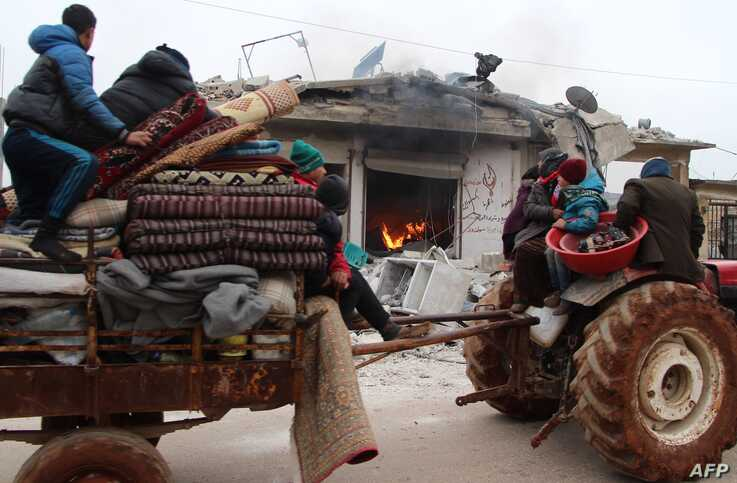 Displaced Syrians pass a house still on fire as they flee shelling on the town of Abyan, in the western rebel-held part of the…