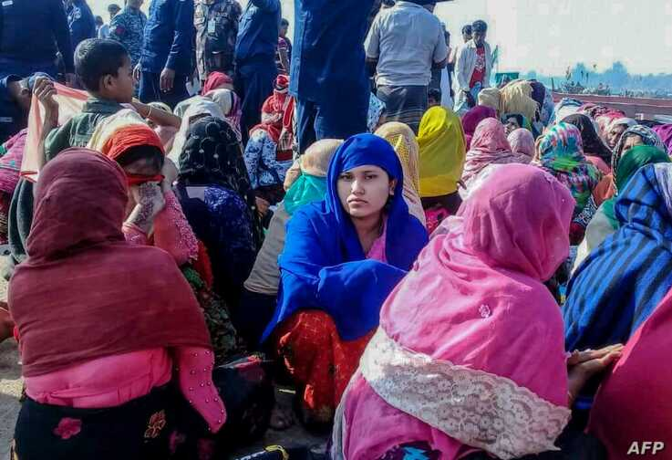 Rohingya refugees wait in an area following a boat capsizing accident, in Teknaf on February 11, 2020. - At least 14 people…