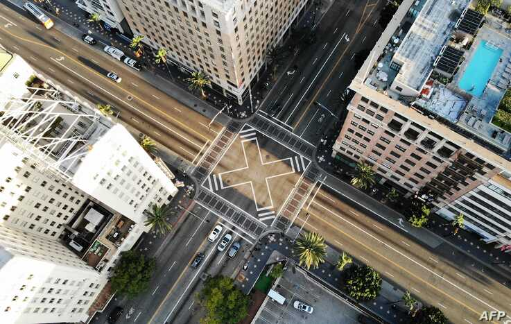 LOS ANGELES, CALIFORNIA - MARCH 25: An aerial view shows the intersection of Hollywood and Vine, shortly before sunset, with…
