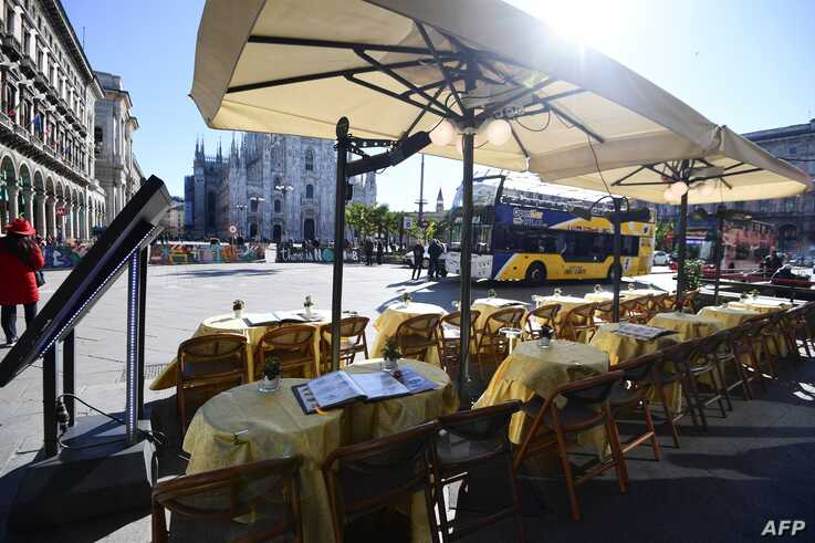 This picture taken on February 27, 2020, shows an empty restaurant in Piazza del Duomo in central Milan. - Italy on Thursday…