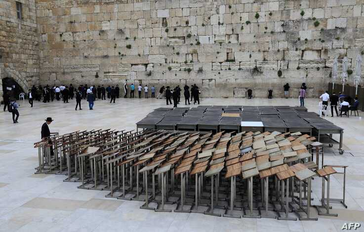 An ultra-Orthodox Jew stands past praying pulpits at the nearly deserted Western Wall, Judaism's holiest site, after Israel has…