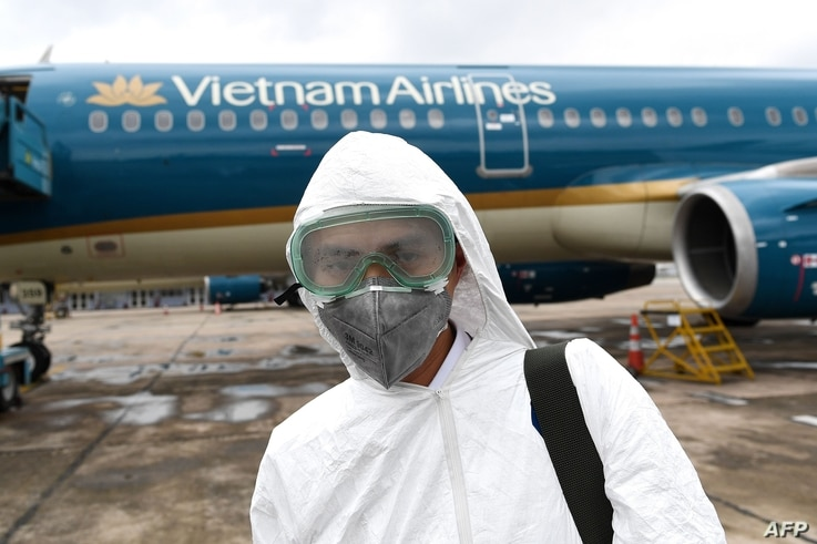 (FILES) In this file photo taken on March 3, 2020 a worker wearing a protective suit prepares to disinfect a Vietnam Airlines…