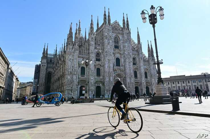 A biker rides past the Duomo di Milano on Piazza del Duomo in central Milan on March 8, 2020, after millions of people were…
