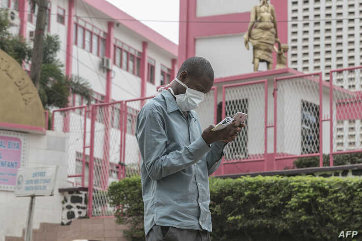 A man wears a mask while walking outside the entrance to the Yaounde General Hospital in Yaounde on March 6, 2020 as Cameroon…