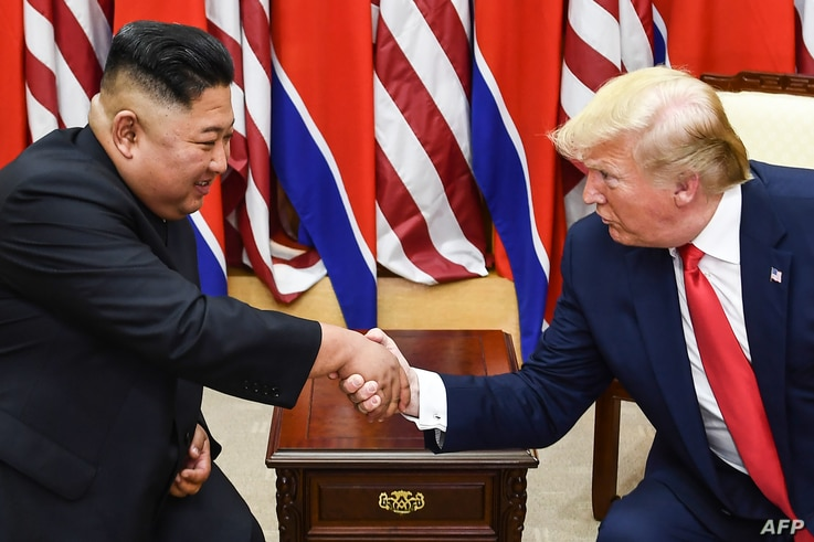 (FILES) In this file photo taken on June 30, 2019, North Korea's leader Kim Jong Un (L) and US President Donald Trump shake…