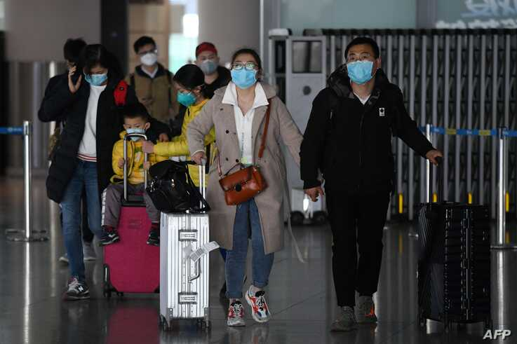 Passengers arrive from a domestic flight at Beijing Capital Airport on March 27, 2020. - China will drastically cut its…
