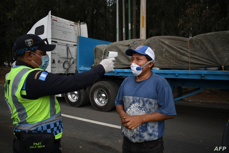 A transit police officer checks the temperature of a truck driver as a preventive measure against the new coronavirus, during a…