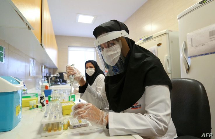 Iranian medical staff work on the production of COVID-19 test kits at a medical center in Karaj, in the northern Alborz…