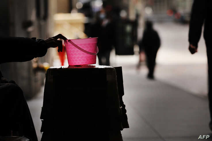 NEW YORK, NY - APRIL 20: A homeless panhandler checks his bucket for money along Wall Street where much of the Financial…