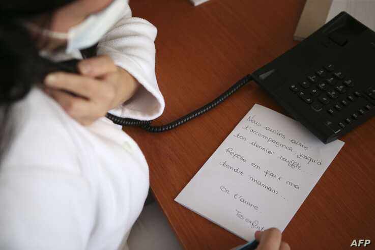 TOPSHOT - A nurse wearing a face masks writes down a message to be put in a coffin as she is on the phone with a deceased…