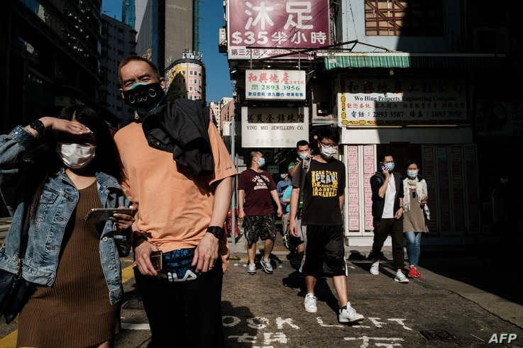 In this picture taken on on April 16, 2020 pedestrians wear face masks, as a precautionary measure against the COVID-19…