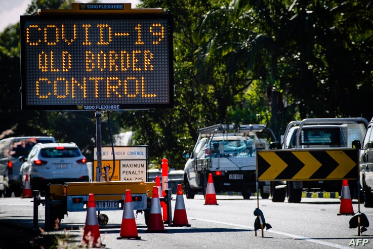 A COVID-19 signage is seen at a vehicle checkpoint on the Pacific Highway on the Queensland - New South Wales border in …