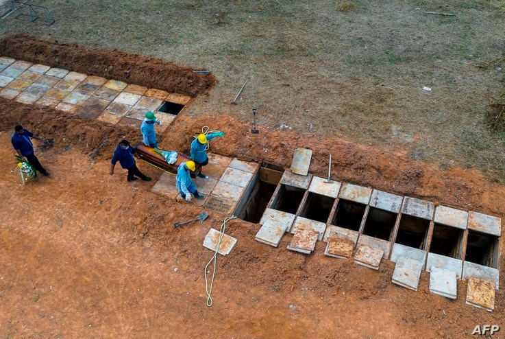 (FILES) This file photo taken on May 07, 2020 shows an aerial view of a burial at the Bom Jardim cemetery, the largest public…