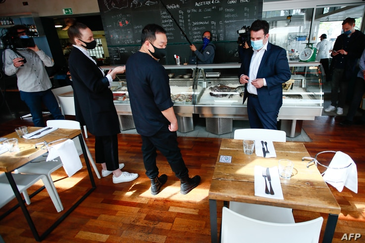 """German Labour Minister Hubertus Heil (R) wears a face mask as he talks to staff during his visit at the restaurant """"Funky Fish""""…"""