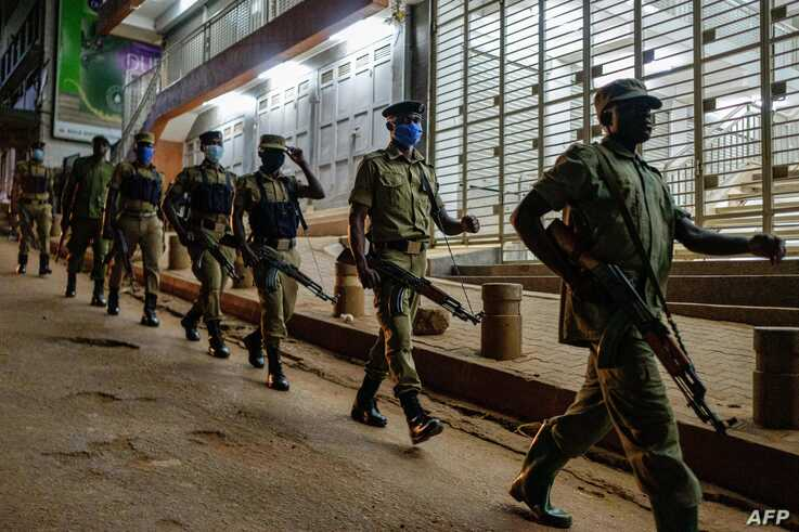 Ugandan police officers and members of Local Defence Units (LDU), a paramilitary force composed of civilians, patrol during the…