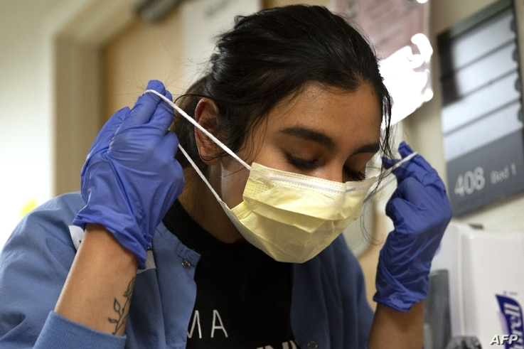 SEATTLE, WA - MAY 07: Charge nurse Liliana Palacios carefully removes her mask and PPE after tending to a patient with COVID-19…
