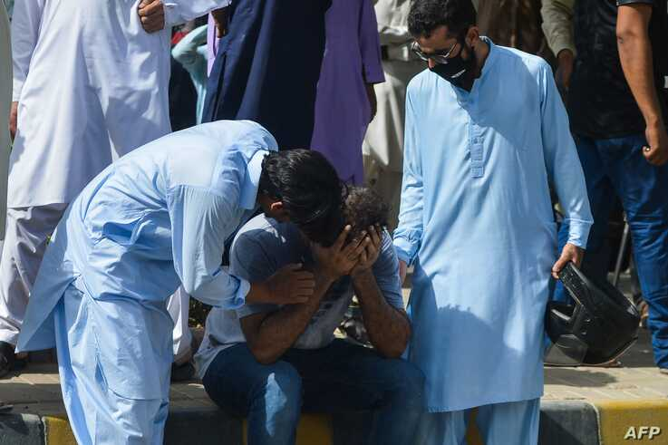 People comfort a relative of a victim near the site after a Pakistan International Airlines aircraft crashed in a residential…