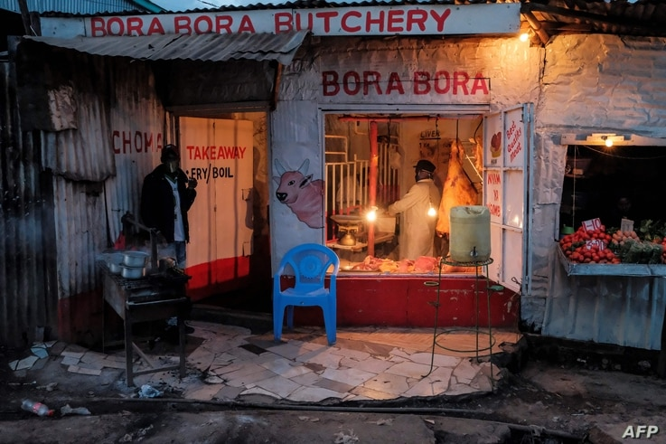 A butcher makes a fresh cut of meat for a customer just before the 7PM curfew in Kibera, Nairobi on May 05, 2020. - The Kibera…