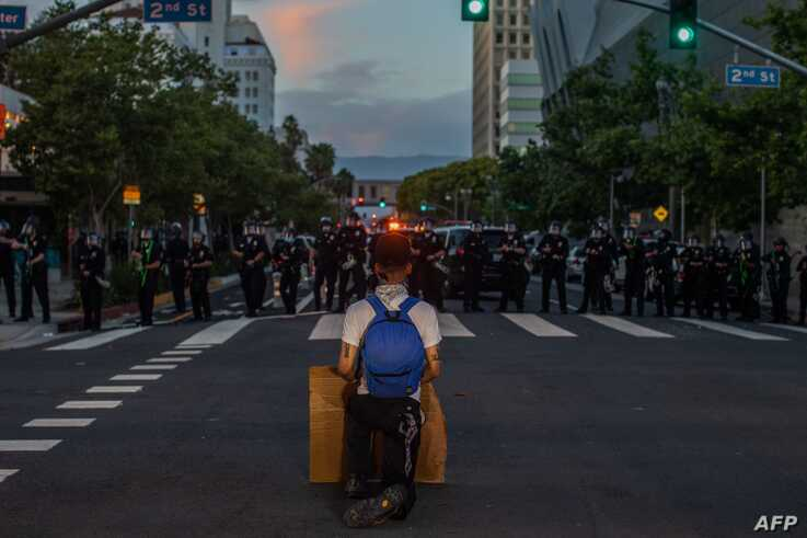 A demonstrator kneels in front of a Police line in Downtown Los Angeles on May 30, 2020 during a protest against the death of…