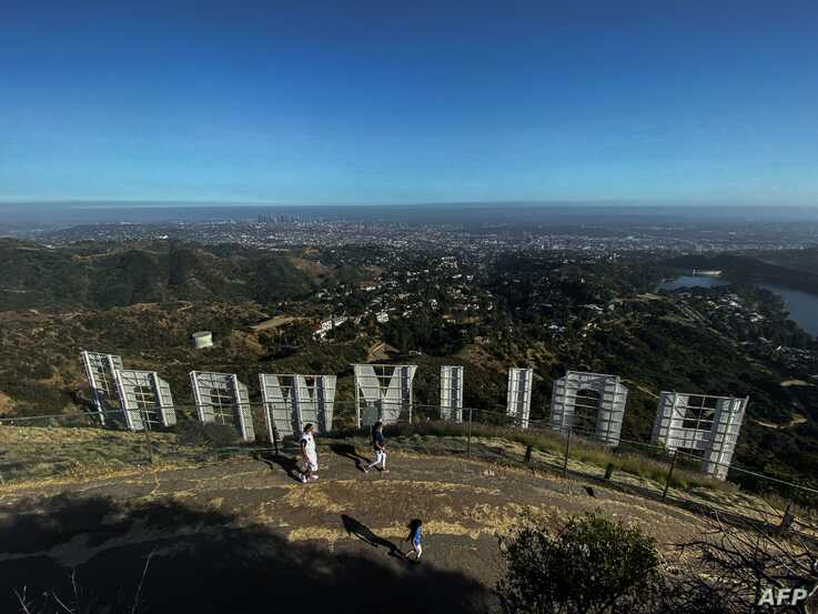 (FILES) In this file photo taken on May 24, 2020 a family wearing face masks, hike at Griffith Park at the back of the…