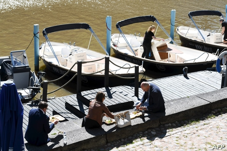 People enjoy their lunch on a sunny May 28, 2020 by the River Aura in Turku, Finland amid the novel coronavirus pandemic. …