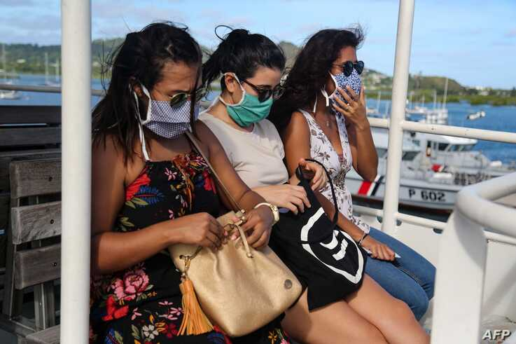 Passengers wearing protective face masks travel by boat to Petite-Terre on the French Indian Ocean island of Mayotte on June 5,…