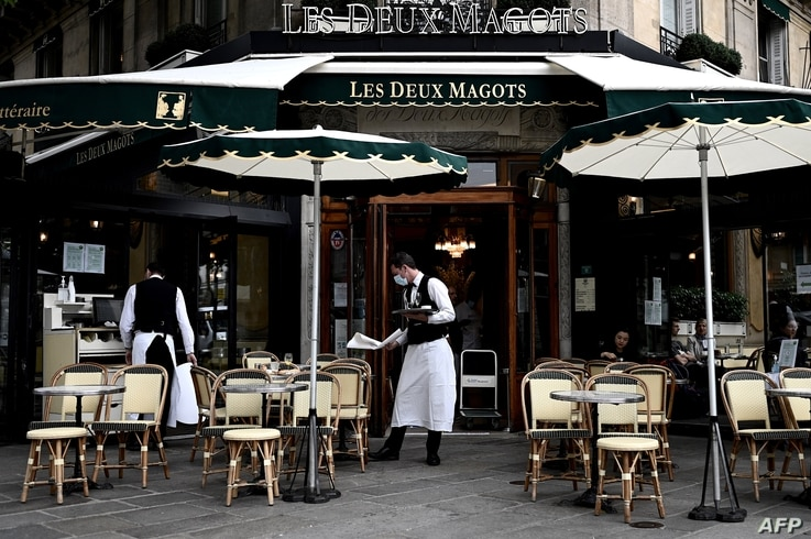 Waiters work at the terrace of a cafe in Paris, on June 15, 2020, one day after French president announced the reopening of…