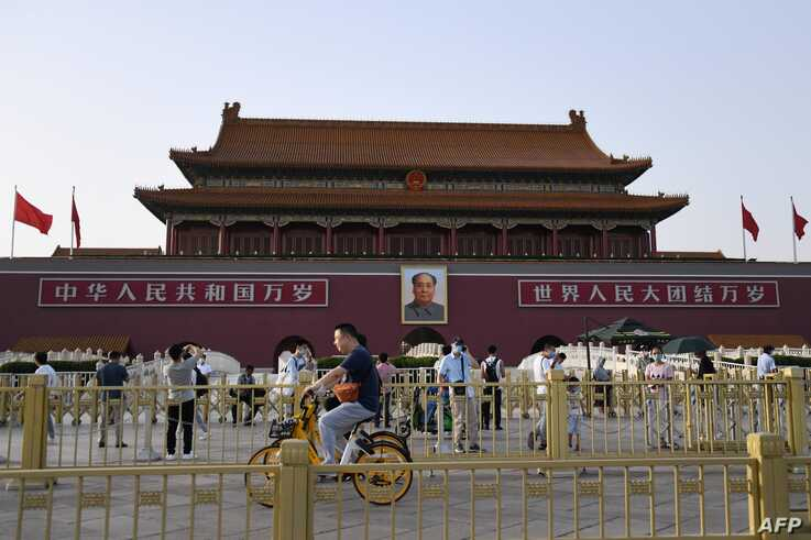 TOPSHOT - People cycle past Tiananmen gate on the eve of the 31st anniversary of the June 4, 1989 crackdown on pro-democracy…