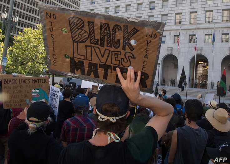 Supporters of Black Lives Matter, hold signs during a protest outside the Hall of Justice as they demonstrate against the death…