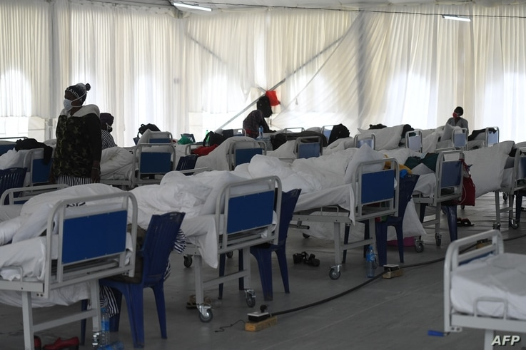 COVID-19 patients rest on their beds at the isolation ward at the Kenyatta stadium where screening booths and an isolation…